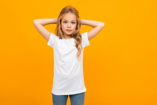 Europees aantrekkelijk meisje in een wit t-shirt met een mockup op een geel