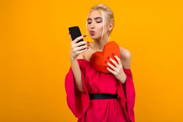 Europees blond meisje in een rode jurk heeft een telefoon met een dating site en heeft een hart gemaakt van papier