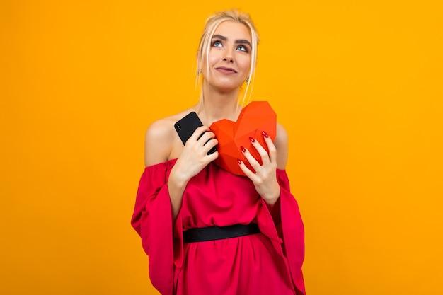 Europees blond meisje in een rode jurk heeft een telefoon met een datingsite en heeft een hart gemaakt van papier