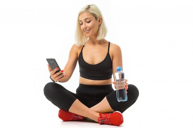 Europees blond meisje in een zwart sport uniform met gele sneakers zit op tapijt met een fles water en een telefoon op wit