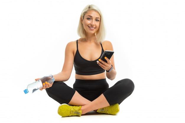 Europees blond meisje in een zwart sport uniform met gele sneakers zit op tapijt met een fles water en een telefoon