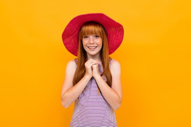 Europees glimlachend meisje in rood panama op een kleurrijk geel