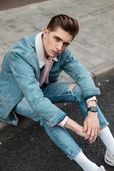 Europees jongemanmodel met kapsel in modieus blauw spijkerjack in stijlvolle gescheurde spijkerbroek in witte sneakers die op tegels in de buurt van de weg rusten. aantrekkelijke man in casual jeugdkleding op straat in de stad.