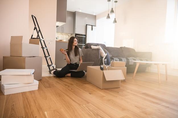 Europees meisje dat pizza eet en thuis laptopcomputer gebruikt. jonge lachende vrouw zittend op de vloer. kartonnen dozen met dingen. concept van verhuizen in nieuwe flat. interieur van studio-appartement. zonnige dag