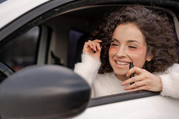Europees meisje in auto brengt mascara aan op wimper met oogborstel. glimlachende krullende vrouw met een ooglapje op het gezicht die naar de autospiegel kijkt. multitasking. moderne levensritme. concept van gezichtshuidverzorging