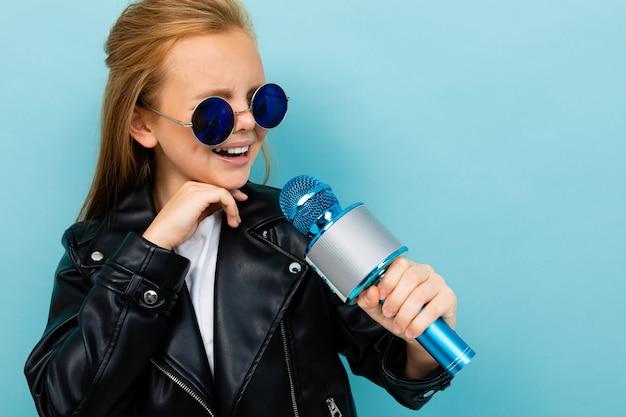 Europees meisje in een leren jas in zonnebril zingen met een microfoon op lichtblauw