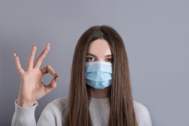 Europees meisje in een medisch masker, toont ok. conceptuele foto over het thema van de covid 2019-pandemie. studio photo.girl geniet van coronavirus veiligheidsbescherming ademhalingsmasker goedkeuren kwaliteit show oké