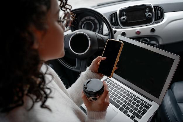 Europees meisje met behulp van mobiele telefoon op de bestuurdersstoel in persoonlijke auto. bijgesneden afbeelding van jonge krullende zakenvrouw met een bril. persoon met laptopcomputer en koffie papieren beker. multitasking