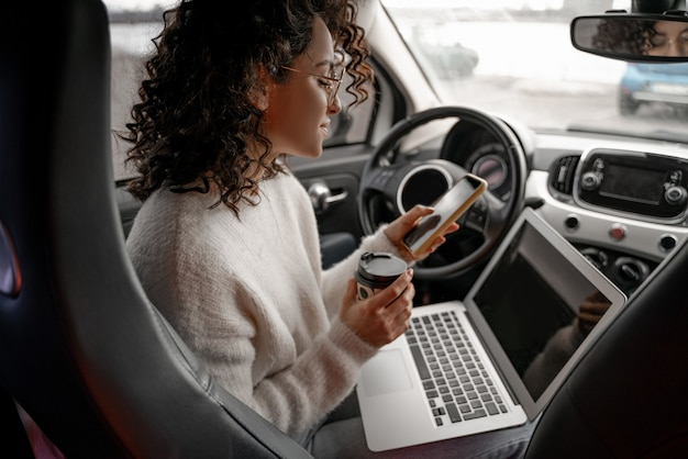 Europees meisje met behulp van mobiele telefoon op de bestuurdersstoel in persoonlijke auto. glimlachende jonge krullende zakenvrouw die een bril draagt. persoon met laptopcomputer en papieren koffiekopje. multitasking