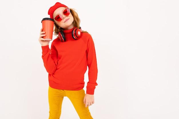 Europees meisje met hoofdtelefoons en zonnebril en een glas in hand koffie