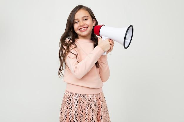 Europees schattig meisje met een megafoon meldt het nieuws met een megafoon aan haar handen op een witte studiomuur