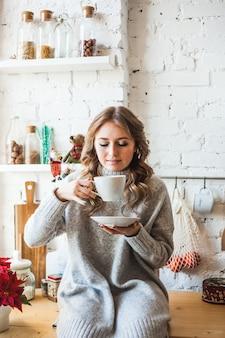 Europees uitziende meisje zit in de keuken, het drinken van thee of koffie uit een witte mok