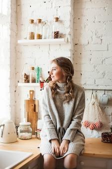 Europees uitziende meisje zit in de keuken, koken, koffie en thee