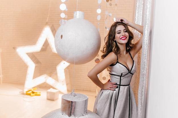 Europees vrouwelijk model met mooie krullen in feestelijke outfit koket poseren omringd door groot zilveren kerstspeelgoed