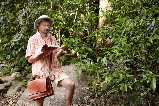 Europese bioloog of ecoloog van middelbare leeftijd met een hoed en aktetas die aantekeningen in zijn notitieboekje leest tijdens milieustudies buitenshuis, onderzoek doet naar planten, tropisch bos verkent