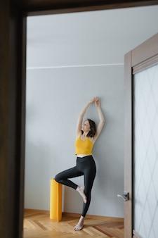 Europese blanke vrouw doet yoga en meditatie in haar huis, kalmerende yoga op een gele mat