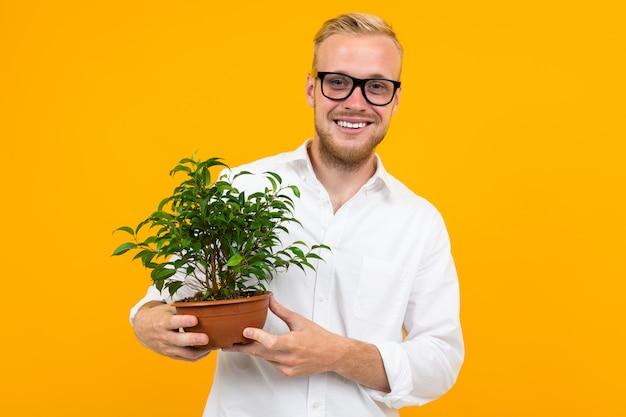 Europese blonde man in een klassiek wit overhemd heeft een potplant op geel