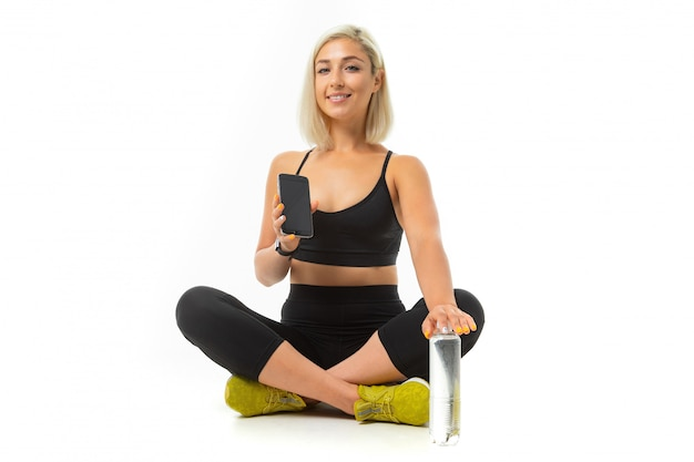 Europese blonde meisje in een zwarte sport uniform met gele sneakers zit op tapijt met een fles water en een telefoon geïsoleerd wit