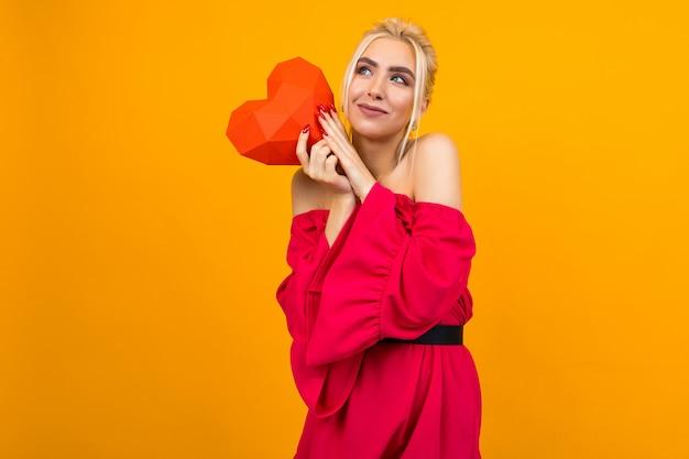 Europese blonde meisje verliefd in rode jurk houdt rood papier hart