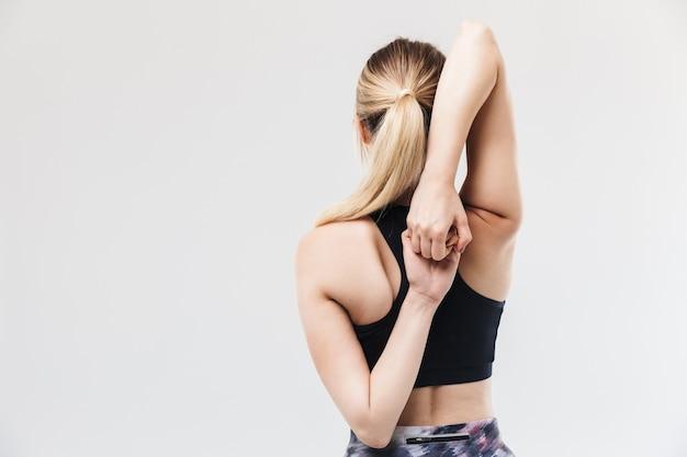 Europese blonde vrouw gekleed in sportkleding die traint en haar lichaam uitrekt tijdens aerobics geïsoleerd over witte muur