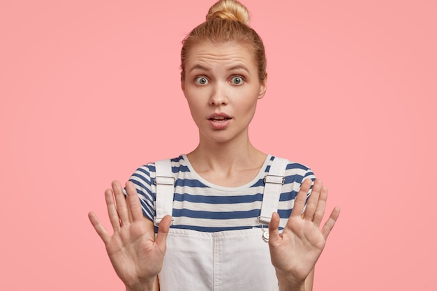 Europese blonde vrouw poseert met uitgestrekte handen, toont een stopgebaar, vraagt om te stoppen, heeft een angstige uitdrukking verrast, eist haar niet lastig te vallen, toont een verbod, draagt een modieuze overall