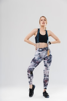 Europese blonde vrouw van volledige lengte gekleed in sportkleding die training doet in de sportschool met springtouw geïsoleerd over witte muur