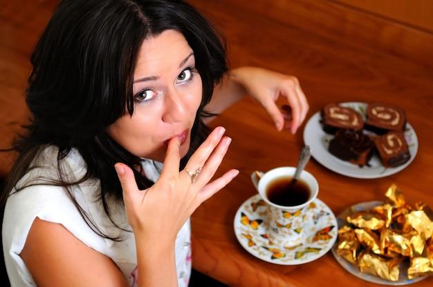 Europese brunette vrouw likt vinger na zoet. kopje thee met lepel op plaat, snoepjes en bakkerij op keukentafel