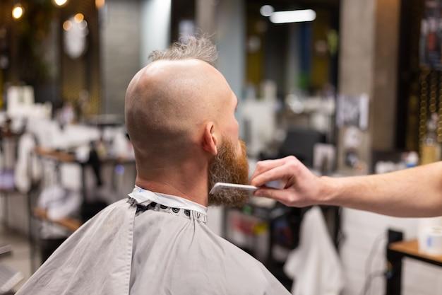 Europese brutale man met een baard geknipt in een kapperszaak Gratis Foto