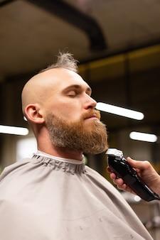 Europese brutale man met een baard geknipt in een kapperszaak