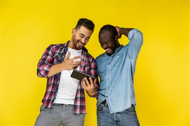 Europese en afro-amerikaanse jongens kijken naar de tablet en lachen