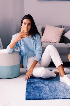 Europese fit brunette fashion blogger vrouw zit op de vloer in de woonkamer in de buurt van bank met telefoon