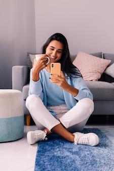 Europese fit brunette fashion blogger vrouw zit op de vloer in de woonkamer in de buurt van de bank