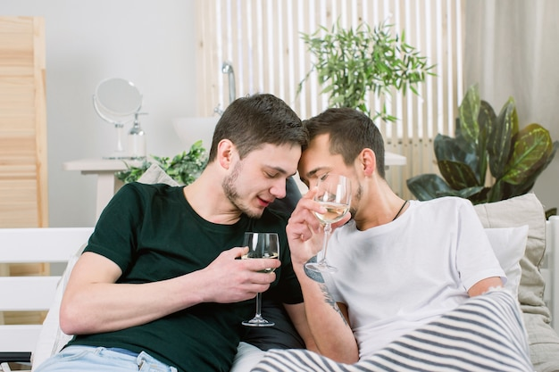 Europese gelukkige homopaar wijn drinken terwijl plezier in bed, strelen. homoseksuele relaties en alternatieve liefde levensstijl concept