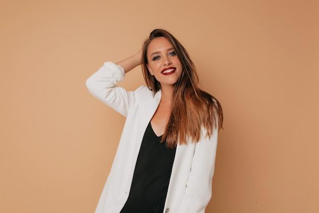 Europese gelukkige vrouw met lichte make-up camera kijken terwijl poseren op beige achtergrond