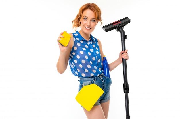 Europese huisvrouw met schoonmaakmiddelen en een stofzuiger in haar handen op een witte muur