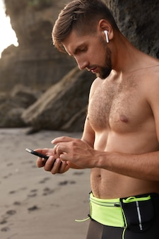 Europese jogger neemt pauze, gebruikt moderne mobiele telefoons, downloadt liedjes in afspeellijst voor training