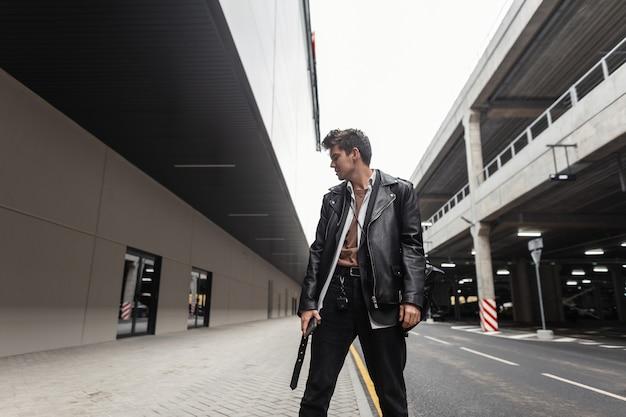 Europese jonge hipster man in trendy zwarte vrijetijdskleding poseren in de stad in de buurt van de weg. stijlvol modern stadsmodel in een vintage leren jas oversized in broek buitenshuis. straat amerikaanse stijl