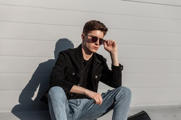 Europese jonge man in modieus zwart spijkerjack in vintage jeans