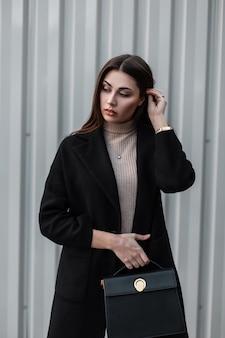 Europese jonge moderne vrouw brunette met lang haar in trendy zwarte jas met modieuze leren tas poseren in de buurt van metalen zilveren muur buitenshuis. europees meisje in de straat. stedelijke dame mannequin.