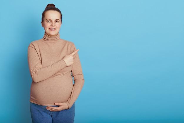 Europese jonge mooie zwangere vrouw buik aanraken met één hand en opzij wijzend met wijsvinger, staande geïsoleerd op blauwe muur, aanstaande moeder met haarbroodje.