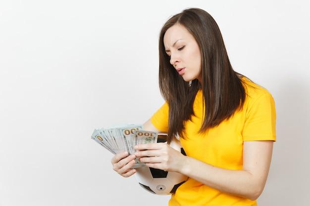 Europese jonge verwarde vrouw, voetbalfan of speler in geel uniform tellen bundel contant geld dollars voetbal geïsoleerd op een witte achtergrond. sport, voetbalspel, opwinding lifestyle concept.