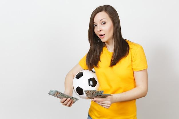 Europese jonge vrolijke vrouw, voetbalfan of speler in geel uniform tellen bundel cash dollars voetbal geïsoleerd op een witte achtergrond. sport, voetbalspel, opwinding lifestyle concept.