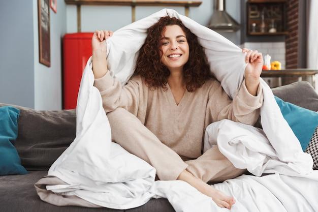 Europese jonge vrouw die huiskleren draagt die glimlachen terwijl ze thuis op de bank zit gewikkeld in een deken