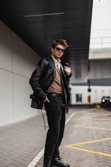 Europese jongeman hipster in coole zonnebril in een mode zwart leren jack in een klassiek shirt in spijkerbroek met een kapsel loopt in de buurt van een grijs gebouw op straat. aantrekkelijke trendy man in de stad