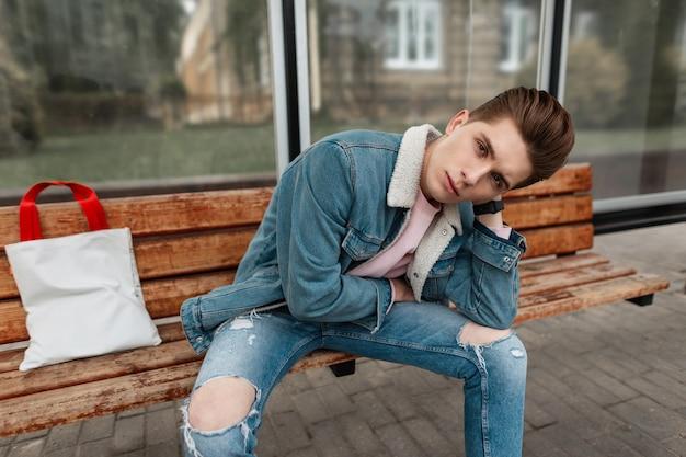 Europese jongeman in stijlvol spijkerjasje in roze t-shirt in vintage jeans met stoffen shopper zit op houten bankje bij halte van openbaar gebouw in de stad. aantrekkelijke man in modieuze kleding op straat.