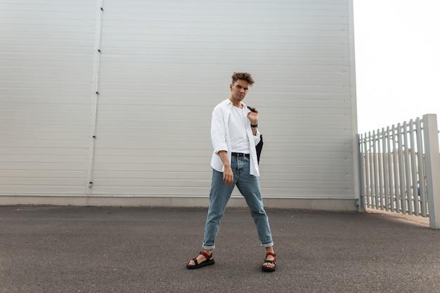 Europese jongeman in trendy wit en denim kleding in modieuze rode sandalen met een vintage tas loopt over de stad.