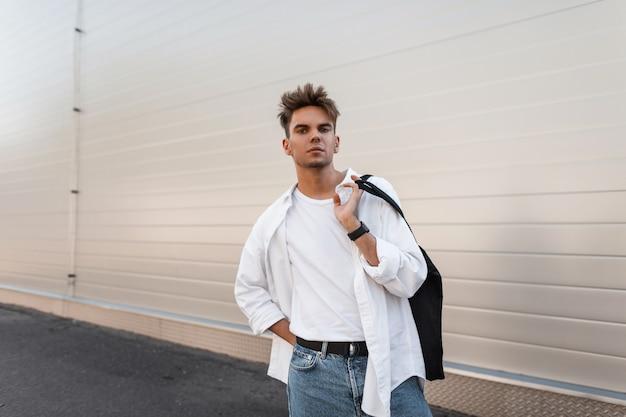 Europese jongeman met een stijlvol kapsel in een trendy wit overhemd in vintage spijkerbroek staat in de buurt van een modern wit gebouw