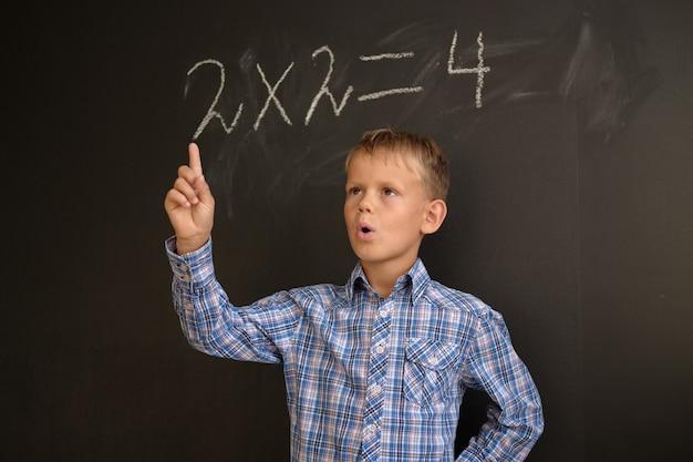 Europese jongensstudent denkt na over de oplossing van wiskundige problemen, staande op een zwarte schoolraad