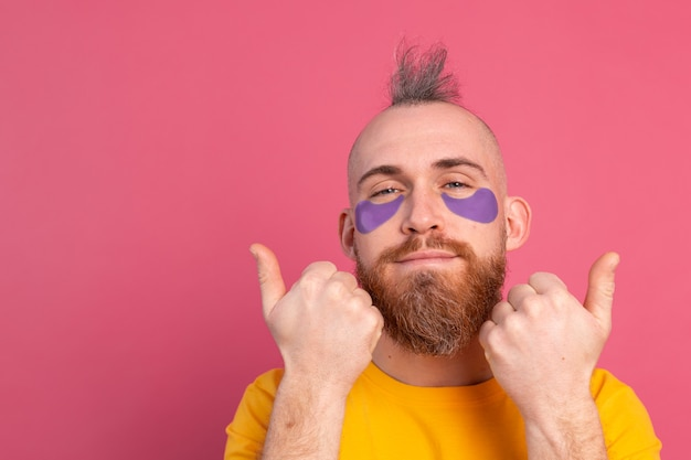 Europese knappe bebaarde man in geel t-shirt en paarse ooglapjes masker op roze