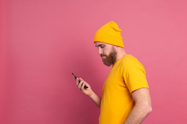 Europese knappe gelukkig vrolijke man met mobiele telefoon op roze